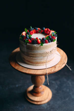 Fruit cake. Cake decorated with berries on a wooden stand on a black background Imagens