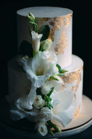 two-tier cake with flowers on a wooden stand on a black background