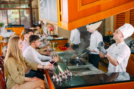 The chef prepares food in front of the visitors in the restaurant Banco de Imagens