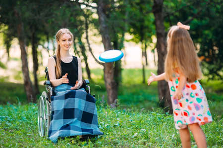 A young disabled girl plays flying disc with her younger sister. Interaction of a healthy person with a disabled person