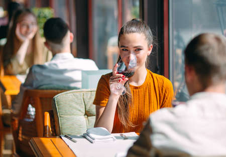 A young couple drinking wine in a restaurant near the window.