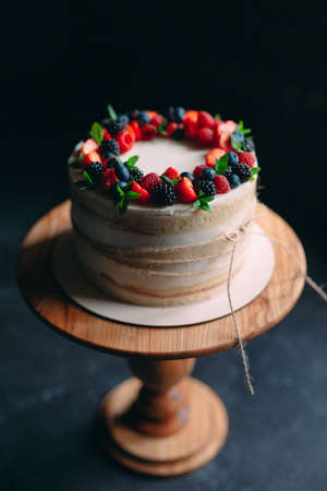 Fruit cake. Cake decorated with berries on a wooden stand on a black background. Imagens - 128596273