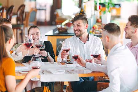 Vrienden drinken wijn op het terras van het restaurant.