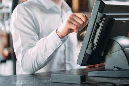 piccola impresa, persone e concetto di servizio - uomo felice o cameriere in grembiule al bancone con cassa che lavora al bar o alla caffetteria.