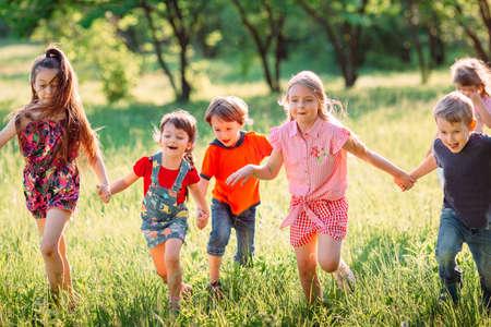 Gran grupo de niños, amigos, niños y niñas corriendo en el parque en un día soleado de verano con ropa casual.