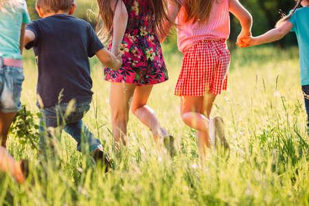 Grande gruppo di bambini, amici ragazzi e ragazze che corrono nel parco in una soleggiata giornata estiva in abiti casual.