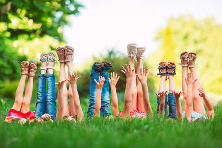 Children lying on green grass in park on a summer day with their legs lifted up to the sky. Banco de Imagens