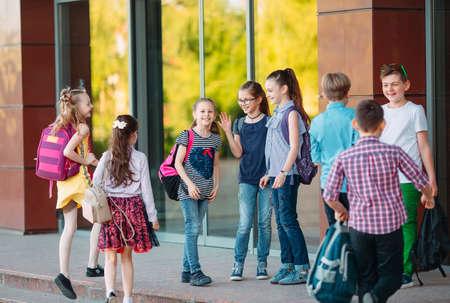 I compagni di scuola vanno a scuola. Gli studenti si salutano. Archivio Fotografico