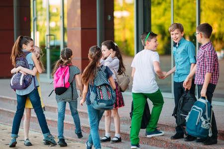 Los compañeros van a la escuela. Los estudiantes se saludan. Foto de archivo