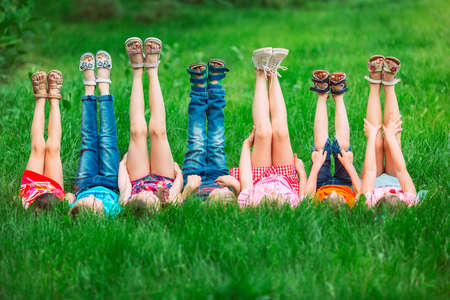 Children lying on green grass in park on a summer day with their legs lifted up to the sky.