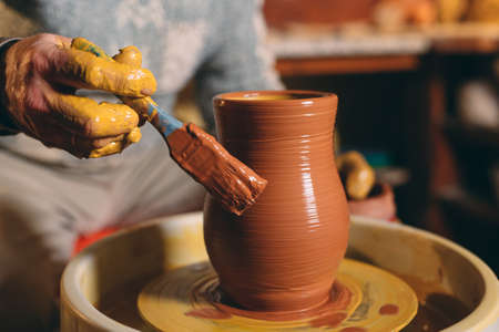 Pottery workshop. A senior man makes a vase of clay. Clay modeling Stock Photo