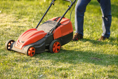 mowing trimmer - worker cutting grass in green yard at sunset. Man with electric lawnmower, lawn mowing. Gardener trimming a garden. Stock Photo