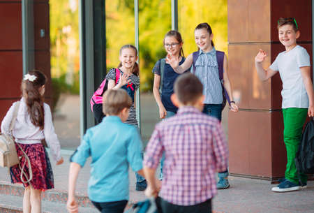 Schoolmates go to school. Students greet each other.