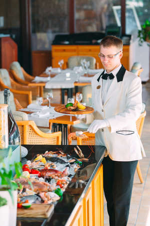 The waiter shifts the seafood on a tray in the restaurant. Фото со стока