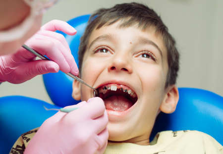 Teenager boy patient at the dentist. A boy with problem teeth sitting in a dental chair.