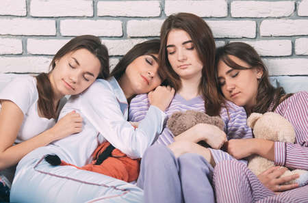 Sleeping group of young people on a bad.