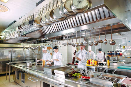 Modern kitchen. Cooks prepare meals on the stove in the kitchen of the restaurant or hotel. The fire in the kitchen