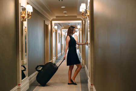 Young woman with handbag and suitcase in an elegant suit walks the hotel corridor to her room.