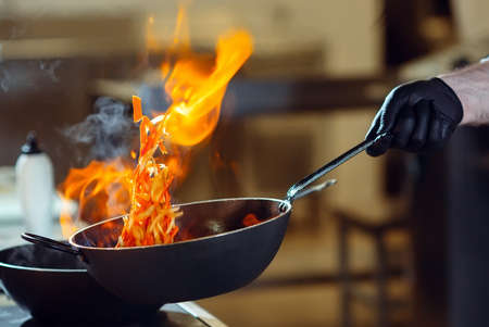 Modern kitchen. Cooks prepare meals on the stove in the kitchen of the restaurant or hotel. The fire in the kitchen. Stock fotó