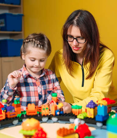 Educational toys for preschool and kindergarten child. Child playing with constructor blocks at class. Imagens