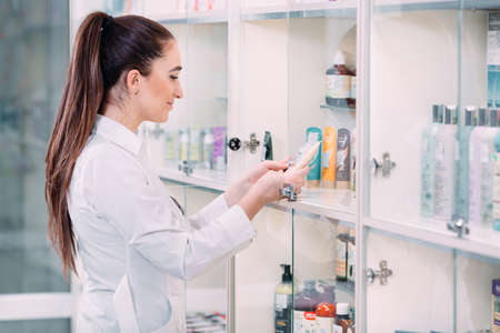 Pretty female pharmacist offering products of body care in pharmacy. Imagens