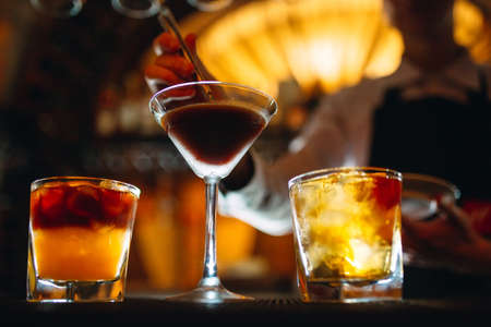 The bartender prepares cocktails at the bar. Stock Photo
