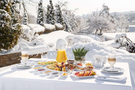 Winter Breakfast pancakes on the terrace outside the restaurant on the background of snow. Pancakes, fruit, juice, and coffee