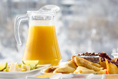 Winter Breakfast orange juice and pancakes on the terrace in front of the restaurant against the snow. Imagens