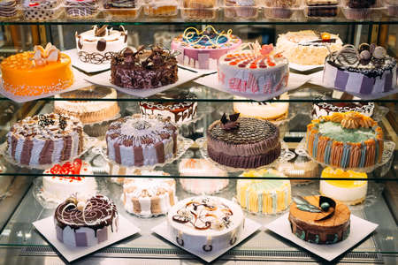 Pastry shop glass display with selection of cream or fruit cake.