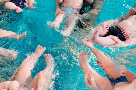 A group of mothers with their young children in a childrens swimming class with a coach.