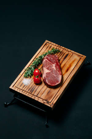 Rib eye steak on a black background.