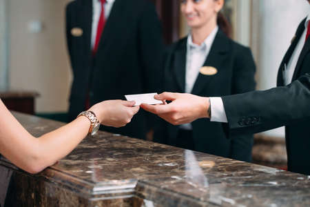 Picture of guests getting key card in hotel.