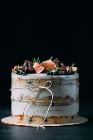 Fruit cake decorated with figs, cookies and blueberries.