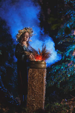 A forest witch brews a potion holding a Voodoo doll.