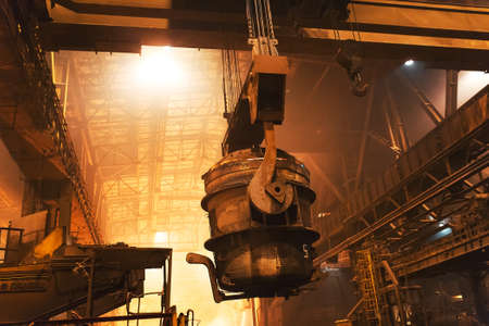 Melting of metal in a steel plant. High temperature in the melting furnace. Metallurgical industry. Factory for the manufacture of metal pipes. Bucket for feeding metal into molds