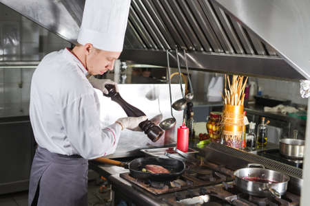 Chef in restaurant kitchen at stove with pan, cooking.