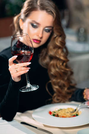 Young beautiful woman drinking wine in a restaurant.