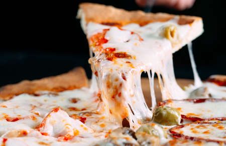 Pizza with very much cheese melting.