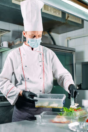 Food delivery in the restaurant. The chef prepares food in the restaurant and packs it in disposable dishes.