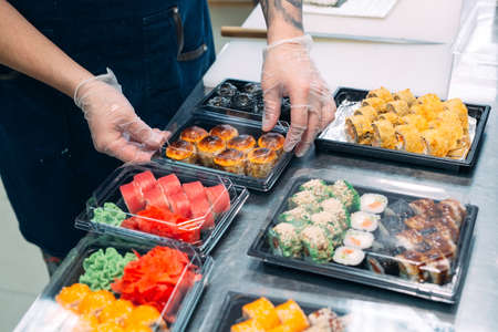 Sushi delivery. Many varieties of Sushi in a plastic box are prepared for delivery.