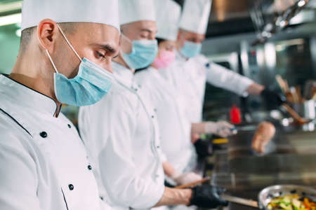 Chefs in protective masks and gloves prepare food in the kitchen of a restaurant or hotel. Stock Photo