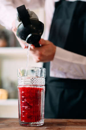 The bartender prepares a berry cocktail on the terrace of the restaurant. Stockfoto
