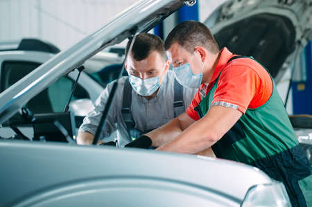 Mechanics in uniform and protective masks work in a car workshop.