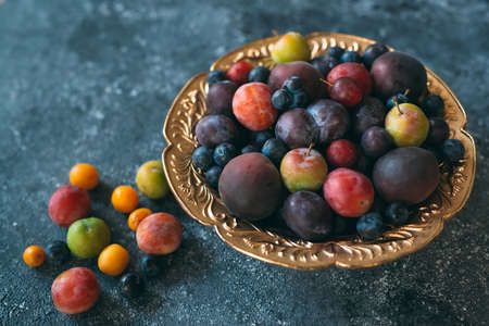 Multicolored plums on a plate are laid out by color.
