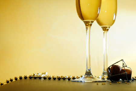 romantic event with two glasses and a necklace and gold background