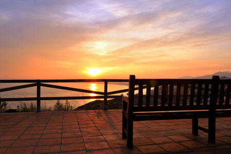 empty bench on a veranda overlooking the sea on a sunset