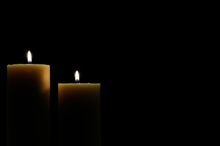 two candles lit with dark background Imagens