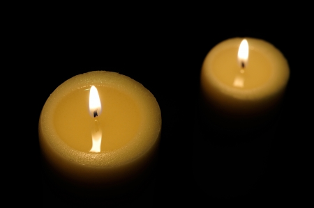 two candles lit with dark background top view