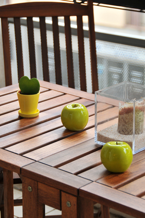 terrace table decorated with two ceramic apples and a plant Stock Photo