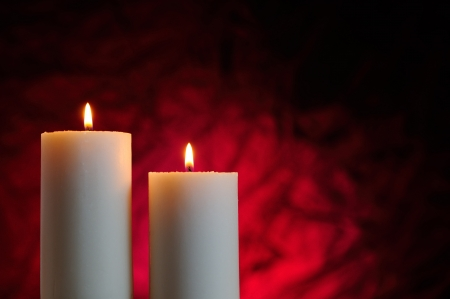 two candles lit with red background Stock Photo - 24642913